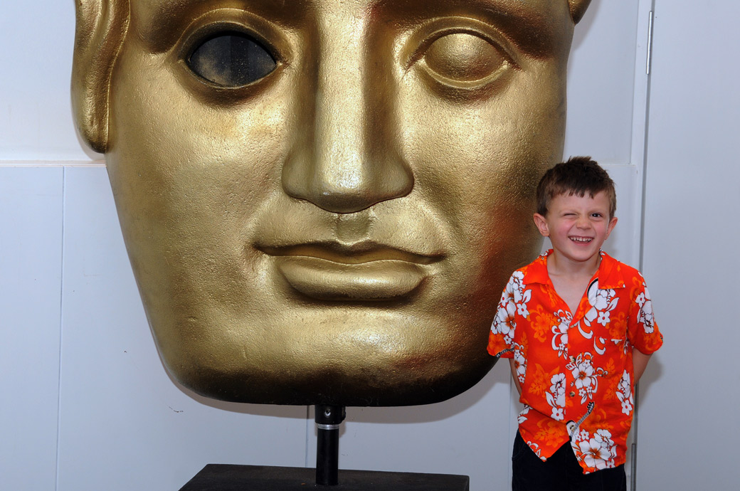A fun boy in bright shirt winking in front of the large bronse Bafta mask wedding photo taken next to the David Laen Room at BAFTA, 195 Piccadilly, London in the Foyer Bar