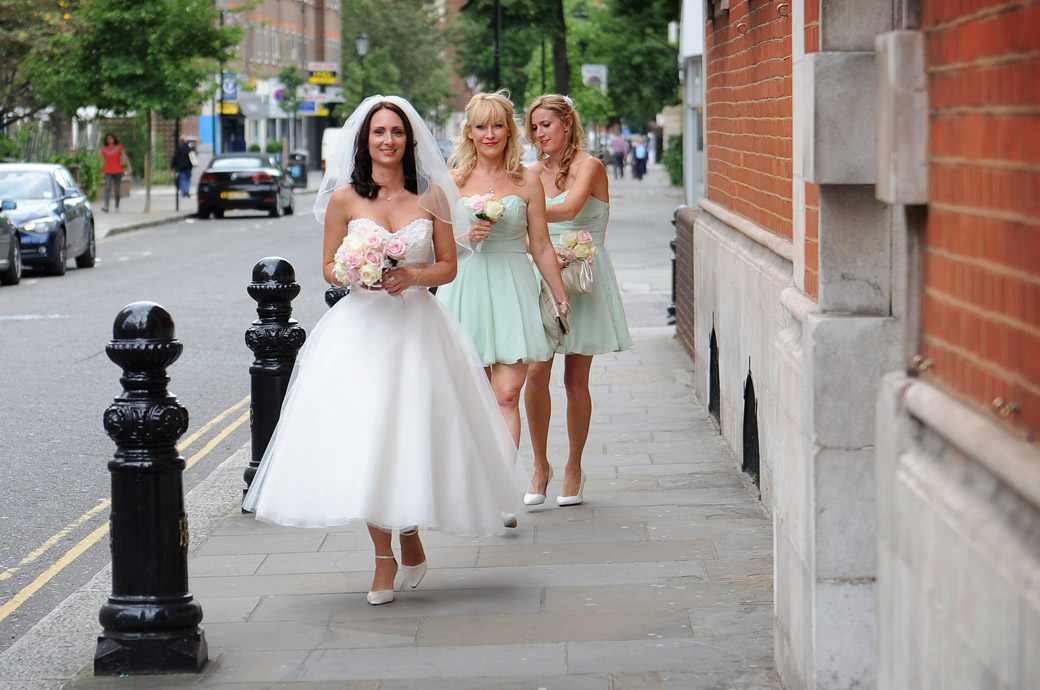 A beautiful smiling Bride walks in her wedding dress towards Chelsea Register Office at Chelsea Old Town Hall a famous wedding venue in London followed by her pretty bridesmaids in green
