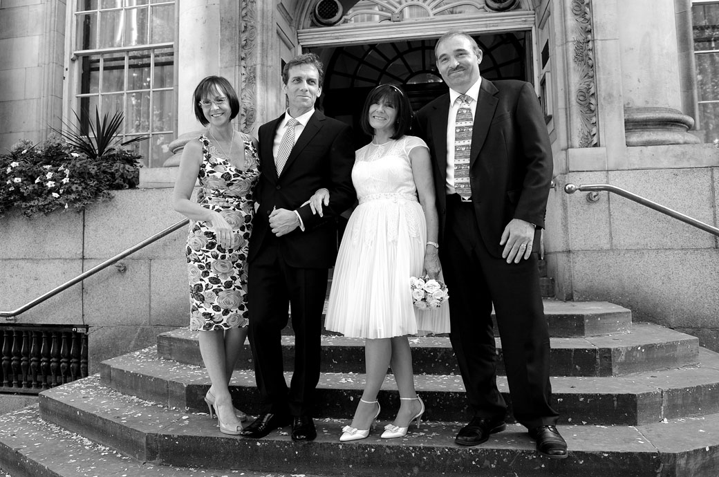 Relaxed small group wedding photograph taken on the famous steps of Chelsea Old Town Hall home to the classic London wedding venue Chelsea Register Office in the King's Road Kensington