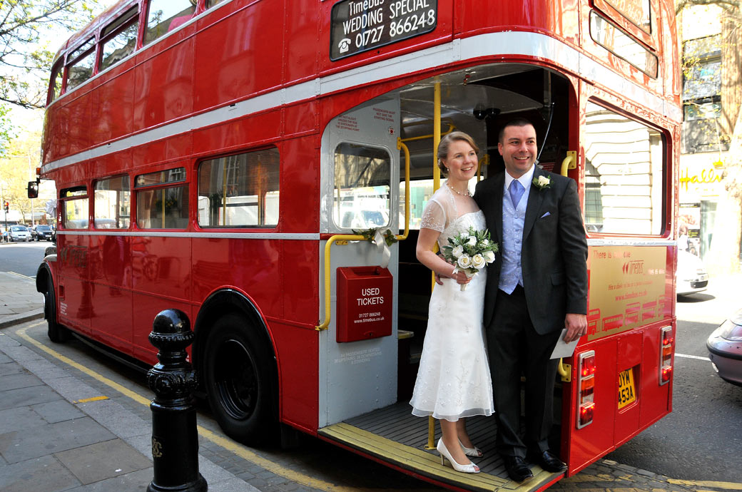 Classic wedding picture of newlyweds outside Chelsea Register Office Chelsea Old Town Hall London standing on the running board of a red double decker wedding bus waiting for their guests to join them
