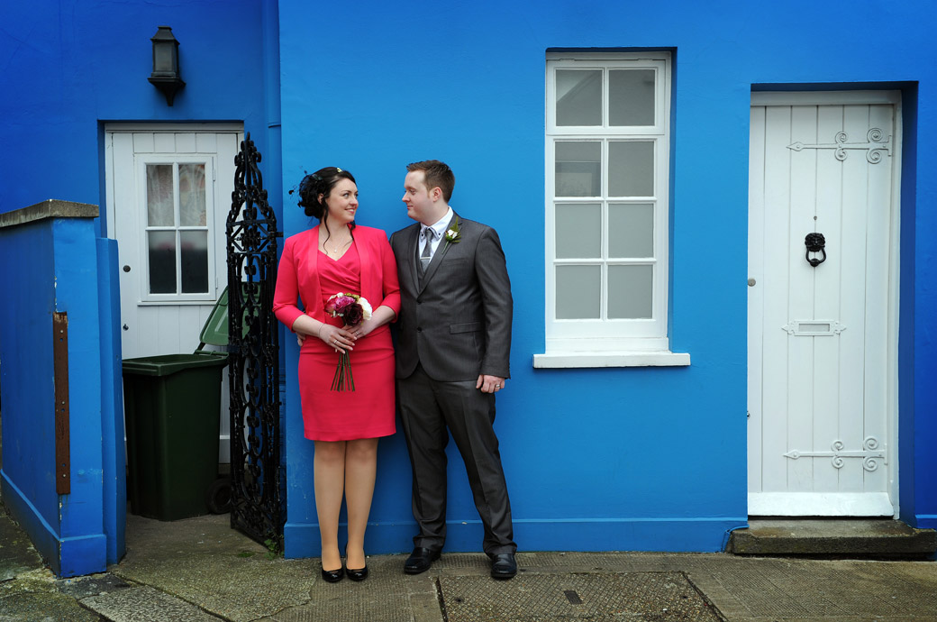 Young newlywed couple after their marriage at Kensington and Chelsea Register Office Chelsea Old Town Hall London in this wedding photo by the bright blue walls of a house off the King's Road