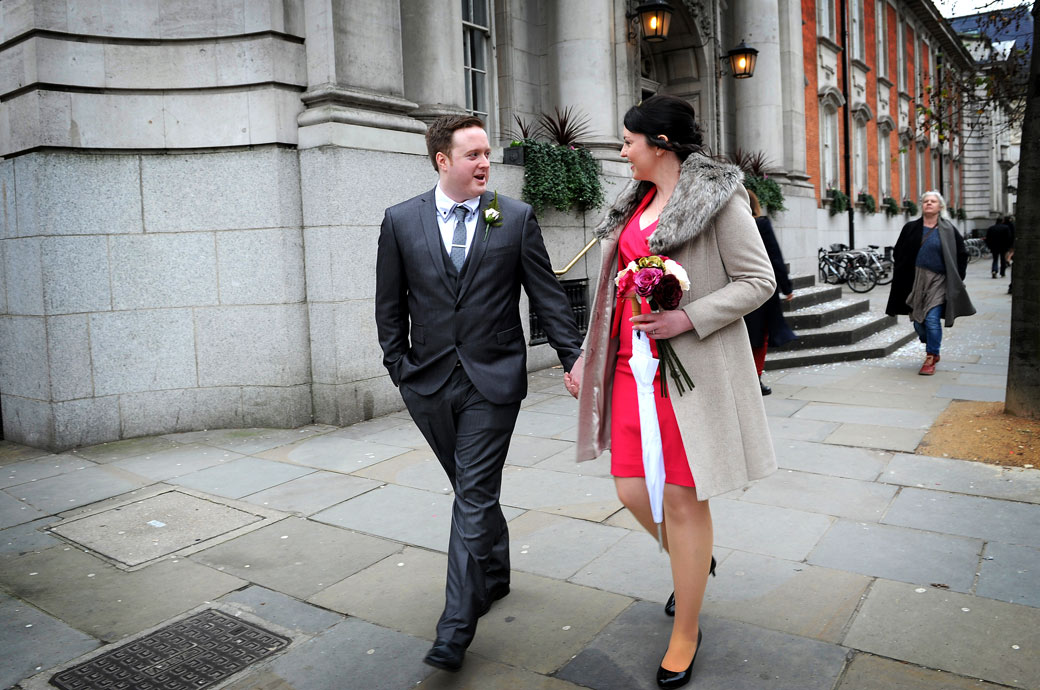 Happy newlyweds walking down the King's Road hand in hand as husband and wife after getting married at the popular wedding venue Kensington and Chelsea Register Office in Chelsea Old Town Hall London