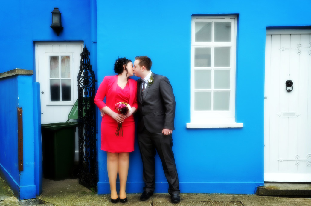After their marriage at the popular and famous Kensington and Chelsea Register Office at Chelsea Old Town Hall in London have a romantic kiss by the bright blue walls of a nearby house