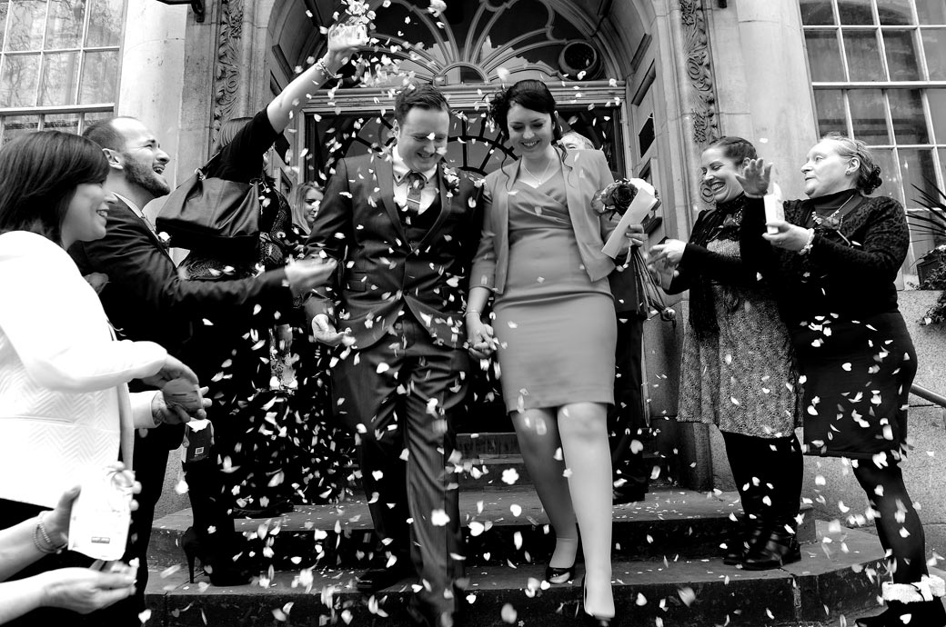 Classic wedding photo of the Bride and the Groom as they depart from London wedding venue Chelsea Register Office onto the steps of the Chelsea Old Town Hall under a shower of confetti