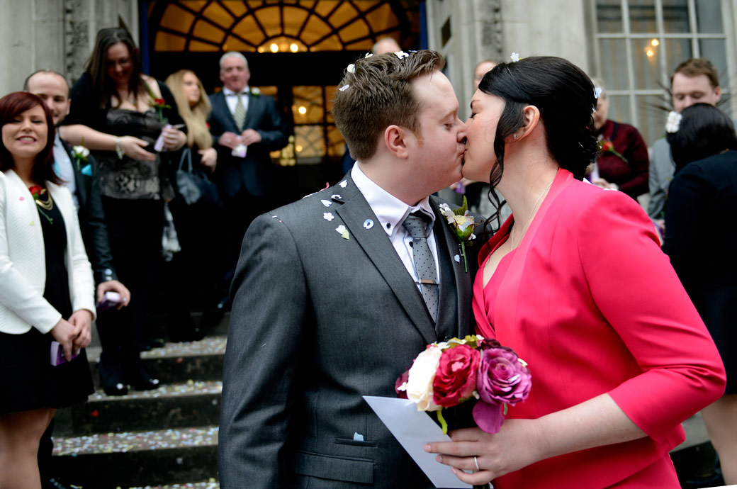 Bride and Groom kiss after walking through the confetti outside London wedding venue Chelsea Register Office at Chelsea Old Town Hall at the bottom of the steps on the King's Road