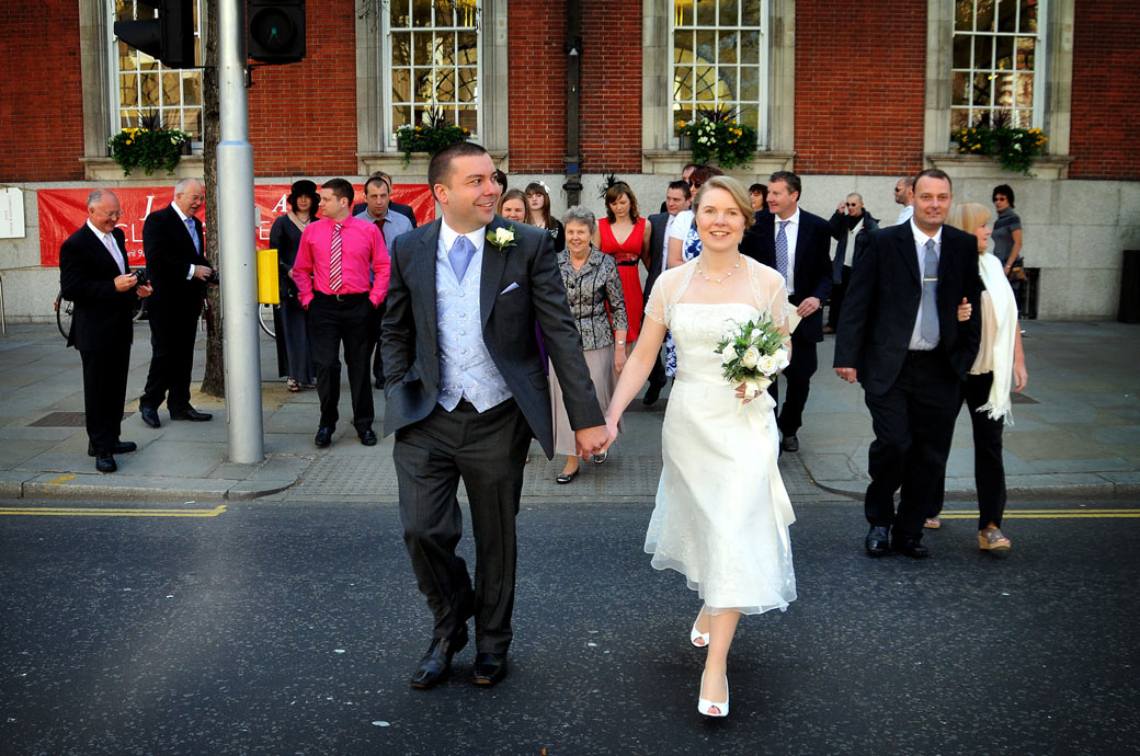 Smiling and happy newlyweds walk across the King's Road captured in this wedding picture as they leave the famous London marriage venue Chelsea Register Office in the Chelsea Old Town Hall
