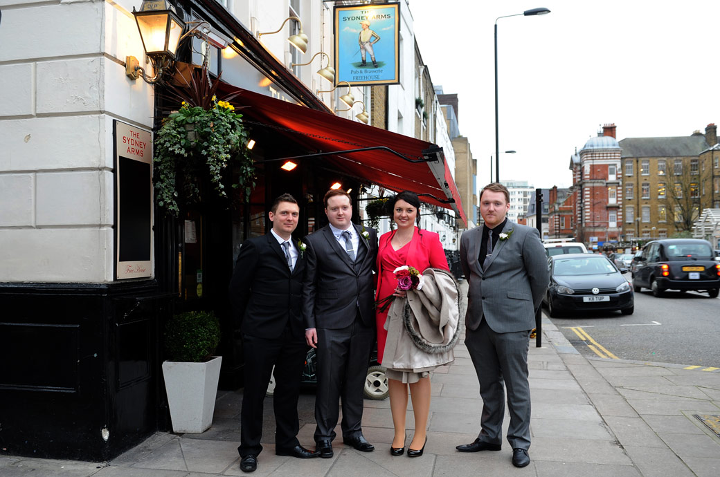 Newlyweds after their marriage at Chelsea Register Office in the Chelsea Old Town Hall London captured in this wedding photo as they pose with friends outside their wedding reception venue The Sydney Arms pub