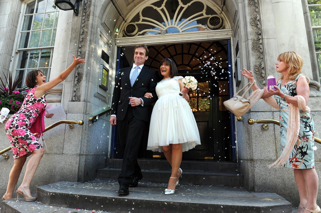 Confetti time for the newlywed couple on those famous steps of Chelsea Old Town Hall home to Chelsea Register Office a hip London wedding venue of worldwide fame