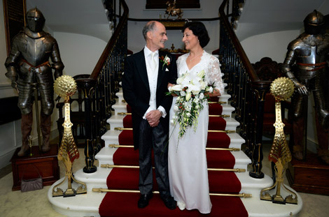 The Bride and Groom's loving looks in this wedding picture taken on the steps of  the impressive staircase at the Armourers' Hall a unique and historic London wedding venue in the City