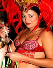Colourful event photography London of a carnival dressed lady in a Brazilian themed fancy dressed Christmas party at the door of Guanabara in Covent Garden
