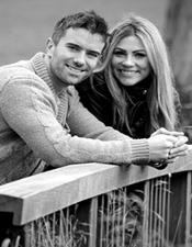 Handsome couple smiling and looking relaxed in this pre wedding photo taken as they lean on a bridge in Brockwell Park South London and watch the world go