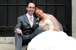 Relaxed wedding photograph of a happy newlywed couple relaxing on the steps outside London wedding venue the  German Church in Kensington