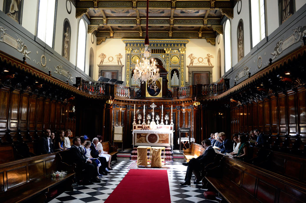 Wonderful wedding photo taken of wedding guests sitting down waiting in the beautiful wood panelled London wedding venue of the Little Brompton Oratory