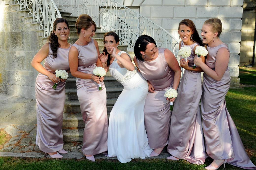Wedding photography London of the Bride and Bridesmaids having fun posing for their group photos at the magestic Parkstead House, Roehampton