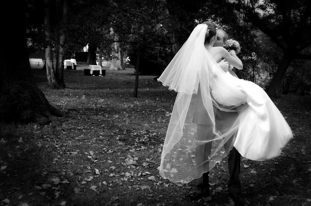 Groom picks his wife up for a romantic kiss under the trees at Pembroke Lodge in Richmond Park wedding photographer Surrey
