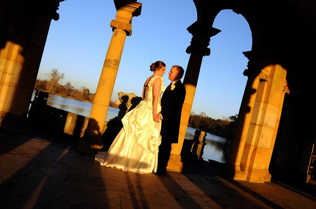 A romantic scene with the Bride and Groom holding hands by the Italian Loggia as the sunsets at Hever Castle wedding photographers in Kent