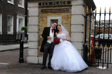 Overjoyed newly-weds portrait wedding picture taken outside London wedding venue St Etheldreda's Church in Ely Place in the City of London