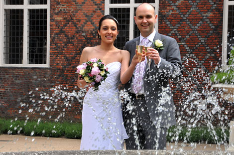 Couple celebrate with champagne captured in this wedding photo taken through the spray of the fountain at the historic London wedding venue Fulham Palace