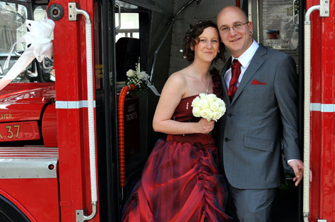 Bride in red stands smiling with her Groom on the steps of a double decker bus in this wedding photo taken outside Islington Town Hall Register Office