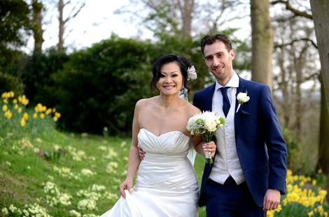 Joyful smiling London Bride and Groom captured as they have a romantic walk through the daffodil filled woods aftre their marriage at Pembroke Lodge Richmond Park