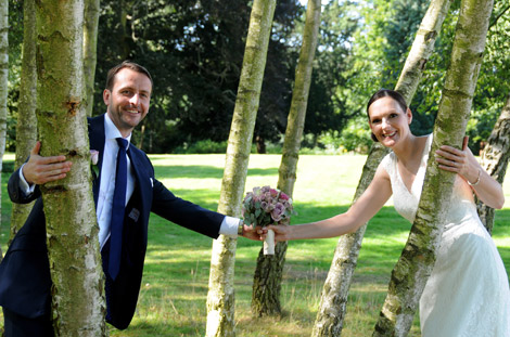 Newly-wed couple having fun amongst the trees at the elegant Buckinghamshire wedding venue Stoke Place situated in the village of Stoke Poges