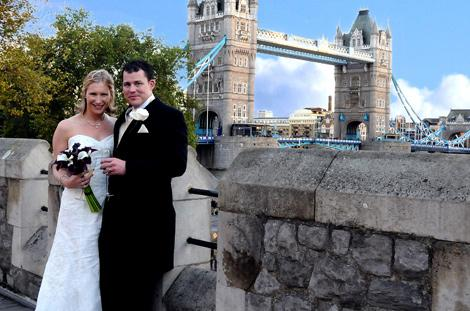 Young newly-weds celebrate on the South Wall at the famous Tower of London in this unique wedding photo taken with Tower Bridge in the background
