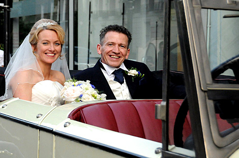 Happy smiling newly-weds captured in this wedding photograph as they ride away in a vintage car after getting married at the London wedding venue Islington Town Hall