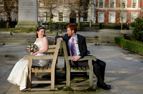Happy young newlywed couple captured in this wedding photograph sitting on a bench in Grosvenor Garden opposite London wedding venue the Millennium Hotel