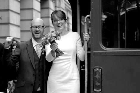 Happy Camden Town Hall newlywed couple celebrate as they stand on the wedding bus ready to go off to their reception at Bush Hall Hammersmith