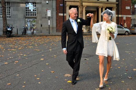Elegant newlywed couple walk hand in hand down the road in this wedding photograph captured after their marriage at Westminster Town Hall Register Office