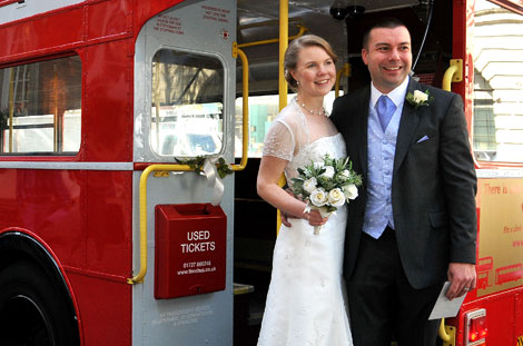 Smiling newlyweds pose on their double decker wedding bus after getting married at Chelsea Old Town Hall Register Office on the famous still swinging Kings Road London