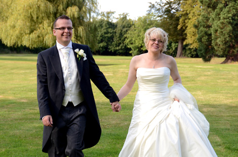 Walking together hand in hand in this lovely happy wedding photograph taken on the lawn at the Kent wedding venue Bickley Manor Hotel