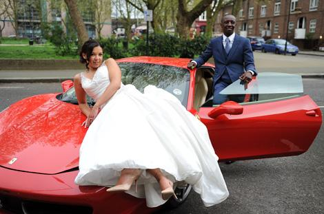 Flash young newlywed couple pose for this wedding picture with their beautiful red Ferrari sports car after getting married at Wandsworth Town Hall Register Office in London