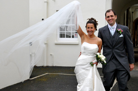 Bride raises her arm standing with the groom and celebrates their marriage in this wedding photograph taken outside London wedding venue Christ Chapel, Dulwich Village