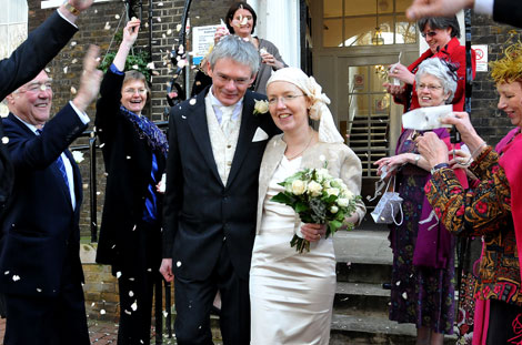 Married couple enjoy themselves during the confetti throwing in this fun wedding picture taken on the steps of London wedding venue Southwark Register Office