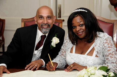Smiling happy couple pose for this wedding photo as they sign the Marriage Register at London wedding venue Wandsworth Town Hall Register Office in the Victoria Room