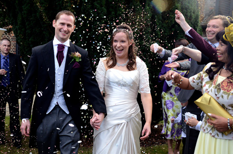 Laughing and smiling couple walking through a shower of confetti in this fun wedding picture captured on the lawn at the Tudor Barn London wedding venue in Eltham