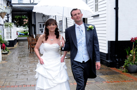 Wedding photograph of couple walking through the courtyard in the rain with their white parasol at quaint wedding venue The Talbot Inn, Ripley