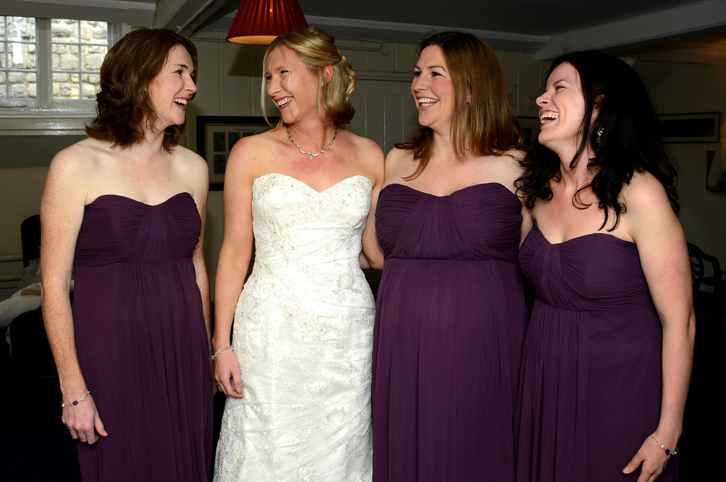 A Tower of London wedding photo of a Bride laughing with her Bridesmaids prior to walking across the cobbles to get married at The Chapel Royal of St Peter ad Vincula a truly historic wedding venue
