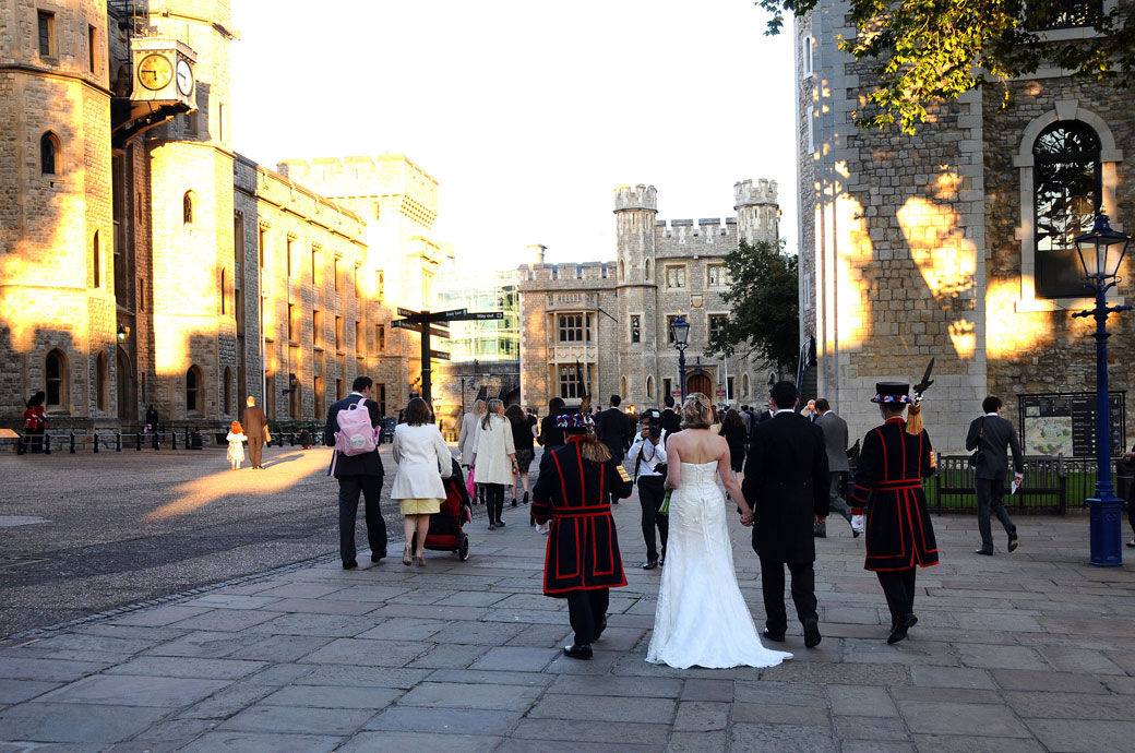 The Bride and Groom walk away from the lawn wedding picture flanked by their Beefeater guard at the unique and magical Tower of London wedding venue in the City