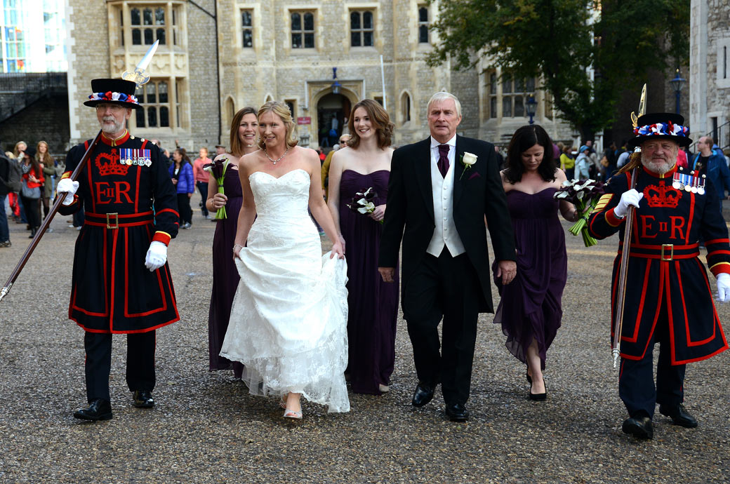 Bride walking with her Father, Bridesmaids and Beefeaters wedding photograph taken on the cobbled courtyard at The Tower of London