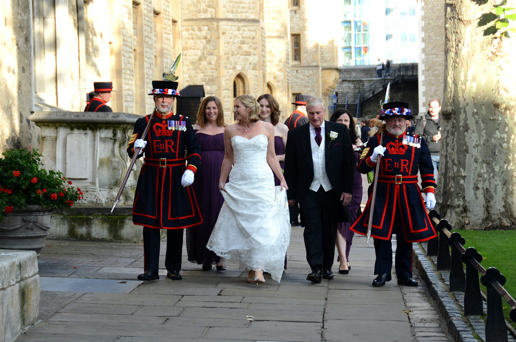 An excited Bride walks with her Beefeater guards wedding photo taken as they approach The Chapel Royal of St Peter ad Vincula at the Tower of London