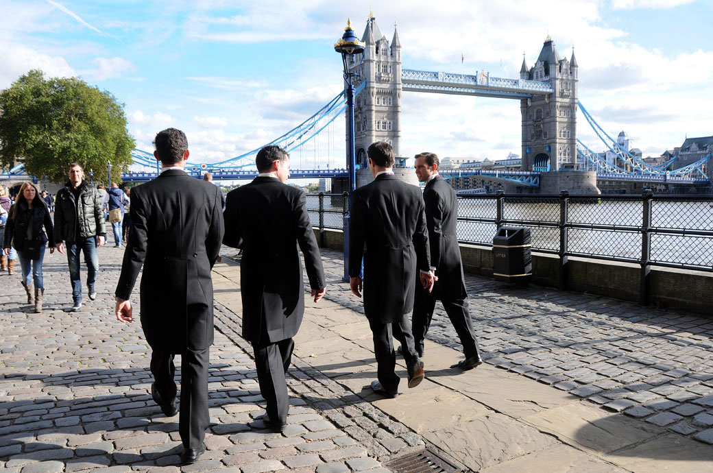 Groom and Groomsmen walking towards Tower Bridge and chatting wedding photo taken at the fabulous Tower of London