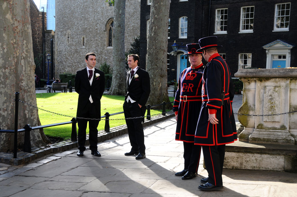 A Groomsmen waiting and the colourful Beefeaters talking wedding picture captured in the grounds of this unique and famous London wedding venue The Tower of London