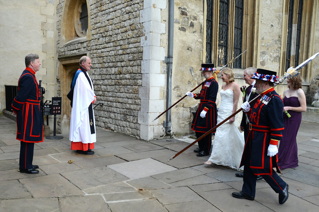 The Bridal party with Beefeaters approaching the chaplain wedding photograph taken outside The Chapel Royal of St Peter ad Vincula at the Tower of London by The Thames