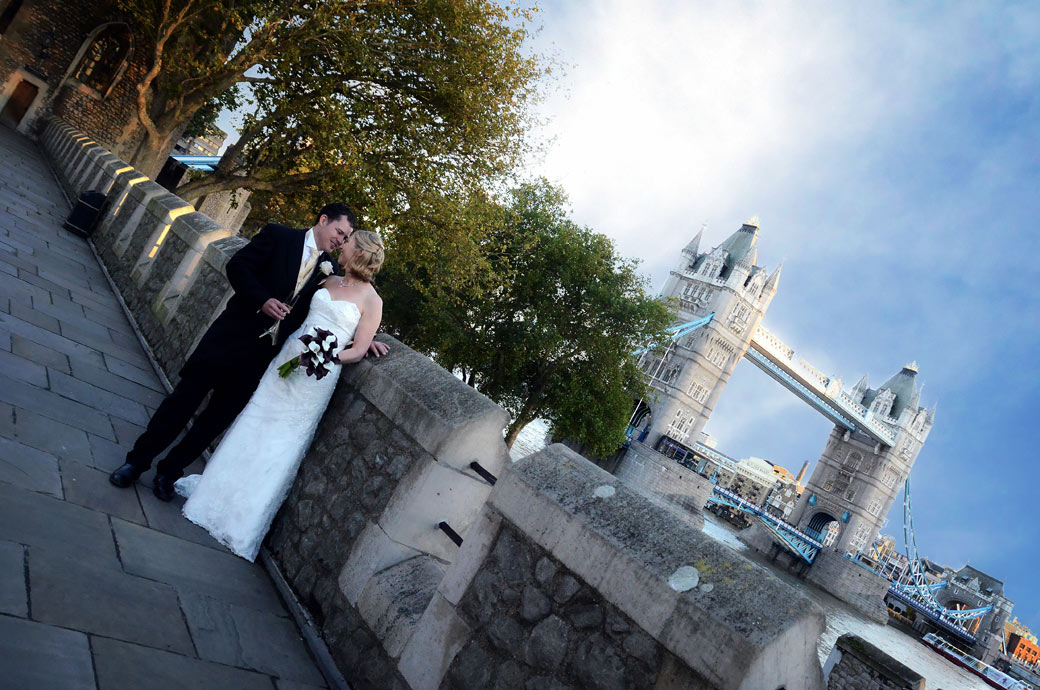 A romantic moment wedding photograph taken on the South Wall of the unique wedding venue The Tower of London with the majestic Tower Bridge in the background