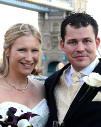 Smiling newly-weds in front of Tower Bridge wedding photograph captured at the stunning historic London wedding venue of The Tower of London