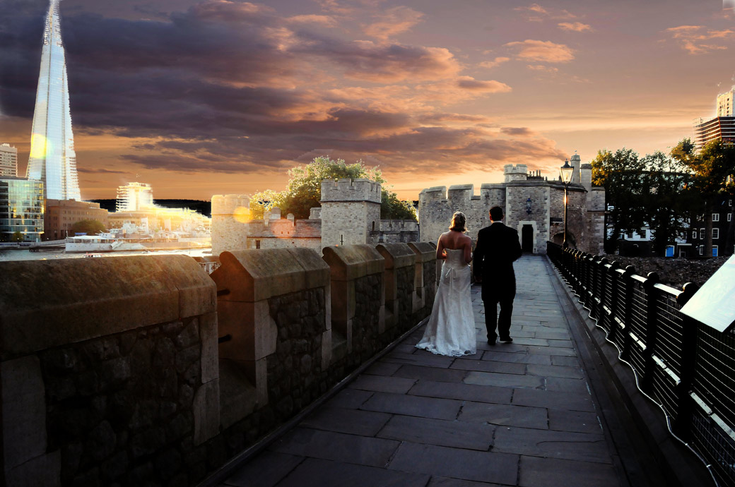 Romantic wedding photograph of the Bride and Groom walking along the South Wall of The Tower of London as the sunsets with the towering Shard in the background