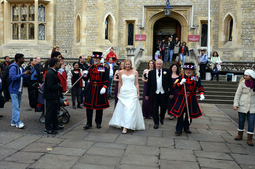 Wedding part walking along the flagstones past the tourists wedding picture taken as they leave the Armoury for the  Chapel Royal of St Peter ad Vincula at The Tower of London