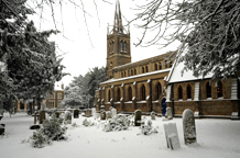 A peaceful and pretty wedding picture taken in the December snow of the graceful All Saints Church Upper Norwood a London wedding venue with some interesting historical connections